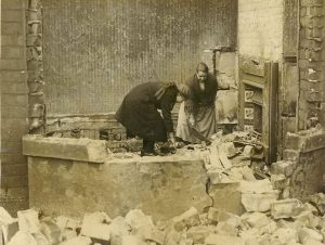 Photograph of mother and daughter sifting through rubble after a fire, illustrating a post about life after the destruction of Jerusalem as depicted in the Biblical Book of Lamentations.