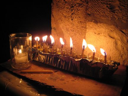 Oil Hanukkiah in Meah Shearim, Jerusalem, with all 8 lights burning, on a table in front of a Jerusalem stone wall. Photo by Andrew Ratto.
