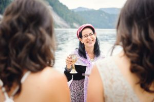 Laura Duhan Kaplan smiling and holding a cup at the wedding of Sam and Anna at Widgeon Lake, BC.