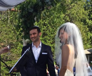 Wedding couple smiling during their backyard wedding ceremony.