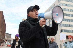 "Man holding megaphone at a political protest rally, illustrating a blog post called ""Dare not to defame."" Photo by Elvert Barnes."
