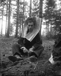 "Man sitting on the ground with a newspaper around his neck, illustrating a post called ""The Book of Job: Election Season Reading."""