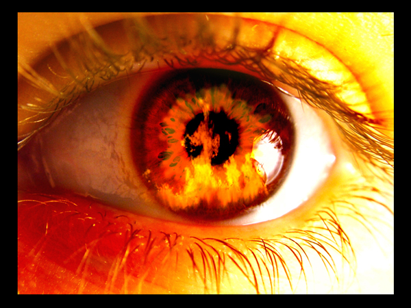 An eye the seems to see fire, with its iris reflecting a yellow and red fire,