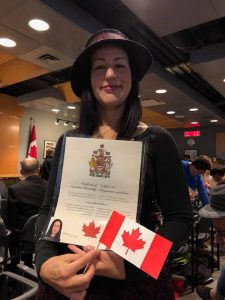 I pose proudly with my with evidence that I am a new citizen of Canada: citizenship certificate and Canadian flag.