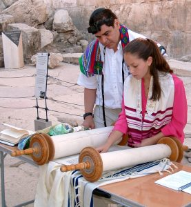 A father and daughter share the ritual of Torah reading at her bat mitzvah ceremony.