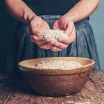 Hands of a woman offering grain from a bowl of raw oats.
