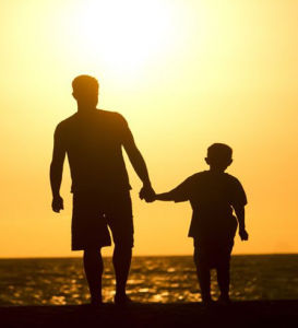 Father and young son in slihouette walking on the beach at sunset to illustrate a post about Biblical Jacob and Joseph.