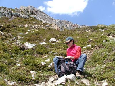 A woman in hiking clothes sits on mountain tundra writing in a notebook about life and love.
