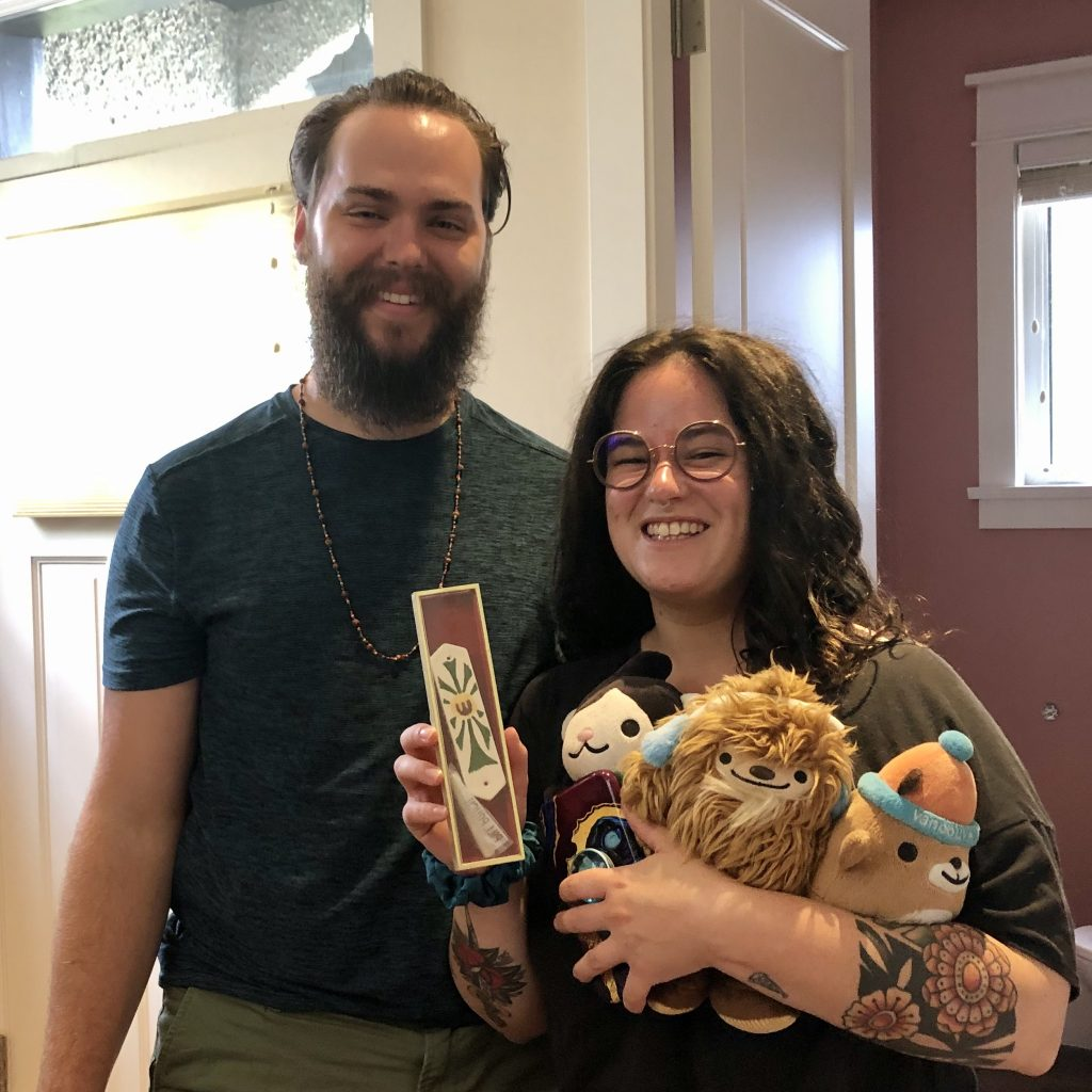 A smiling young woman and young man holding a mezuzah with the text of the Shema inside and also holding three odd stuffed animals, the 2010 Winter Olympic mascots.