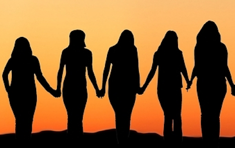 Silhouette of women holding hands against the sunset.