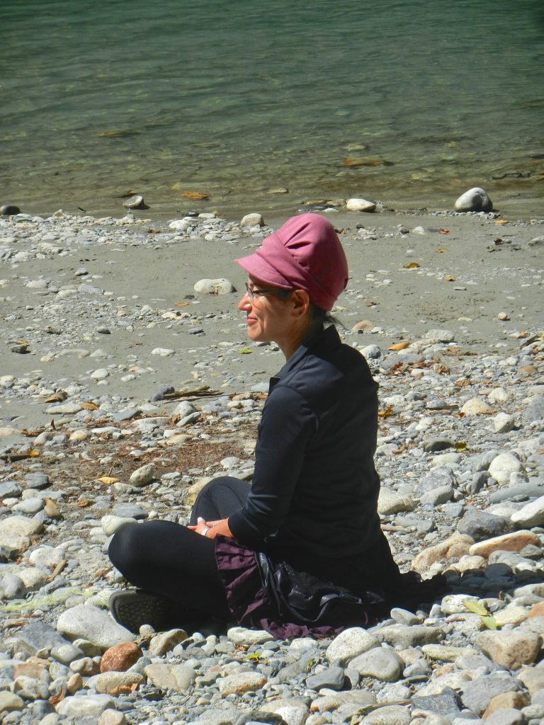 Woman sitting cross-legged on a rocky beach near a glacial stream, smiling as she sits for a creative meditation.