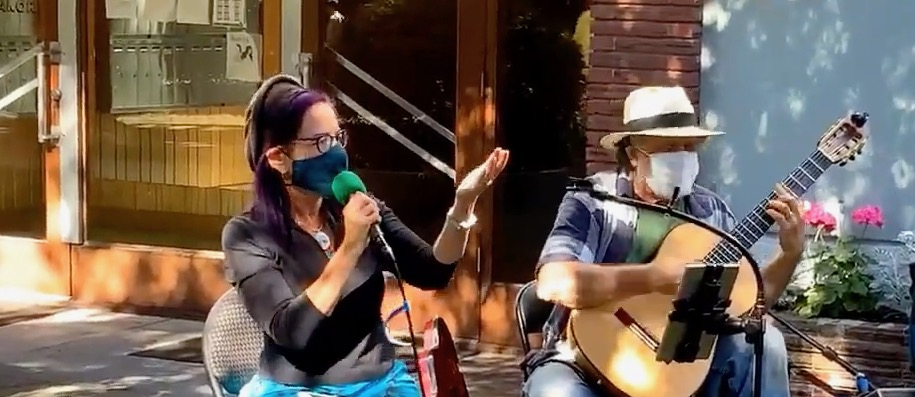 A woman and a man sit outdoors in front of a building, wearing non-medical masks, as the woman speaks into a microphone and the man sits with his guitar ready to play; they are leading a music program in the time of COVID-19.