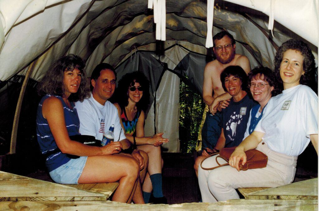 Friends relaxing together in a tent, smiling for the camera.