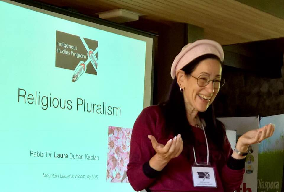 """Laura Duhan-Kaplan laughing in front of a slide that says """"Religious Pluralism, Indigenous Studies Program, Vancouver School of Theology"""""""