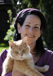 Photo of a smiling woman holding a scowling cat, illustrating an essay about personal spiritual symbols
